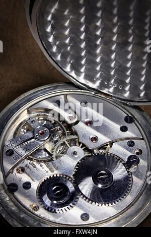 Pocket watch inside on wooden desk with wheels and springs silver color - Stock Photo