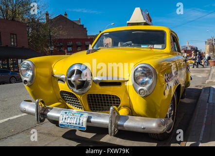 Vintage 1950's era Studebaker yellow taxi cab advertising the Caliente Cab mexican restaurant on 7th Avenue in Greenwich - Stock Photo