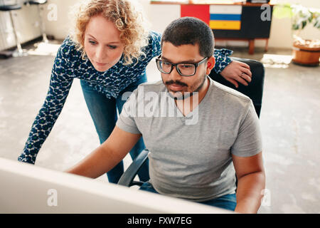 Portrait of two young graphic designers working on computer in office. Male and woman designers looking at computer - Stock Photo
