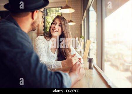 Smiling young woman sitting in a cafe and talking to her boyfriend. Young couple spending time at coffee shop. - Stock Photo