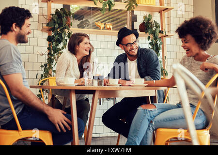 Young people having a great time in cafe. Friends smiling and sitting in a coffee shop, drinking coffee and enjoying - Stock Photo