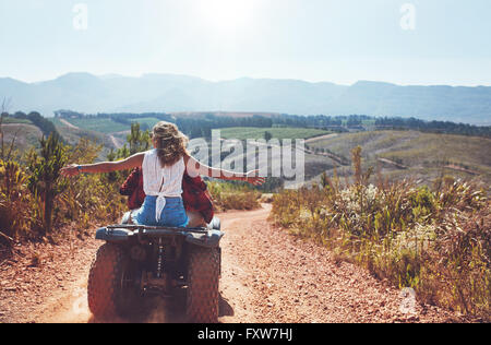 Portrait of young couple in nature on a off road vehicle. Young man and woman having fun on a quad bike in countryside. - Stock Photo