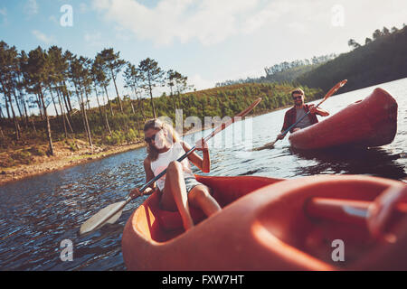 Happy young couple canoeing on lake together. Man and woman kayaking on a summer day. - Stock Photo