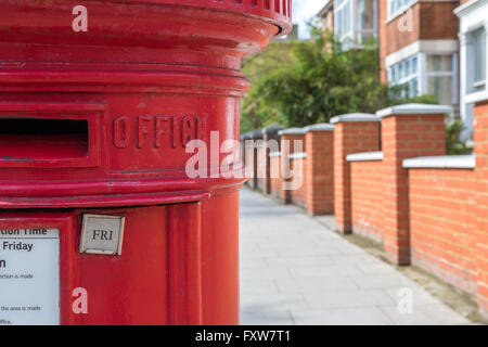 Traditional British post box against blurry terrace house background - Stock Photo