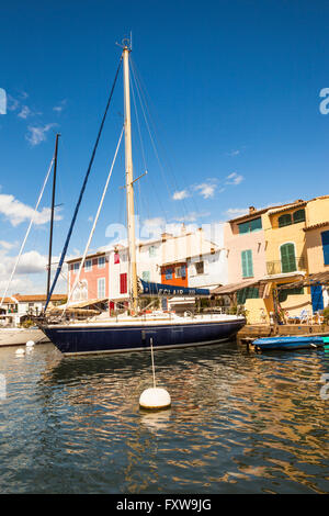 Yacht moored in front of waterfront homes, Port Grimaud, Cote D'Azur, France - Stock Photo