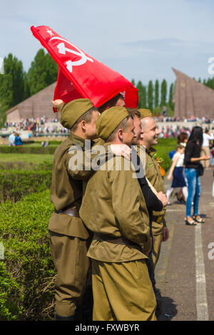 Victory Day in Treptower Park. Soldiers in the uniform of the Red Army during the war, and with the flag of the - Stock Photo