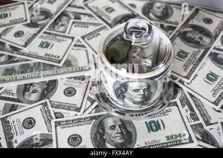 Money in a glass container on the background of one hundred dollar bills. Counterfeit money.