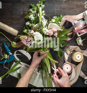 The hands of florist against desktop with working tools and ribbons on wooden background - Stock Photo