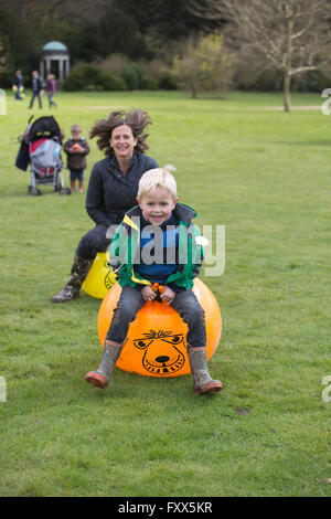 Families having fun on bouncy hoppers outside in the gardens at Hatchlands Park, East Clandon, Surrey, England, - Stock Photo