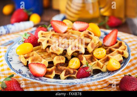 Belgian pumpkin waffles with fresh strawberry, kumquat, honey and cup of coffee - Stock Photo