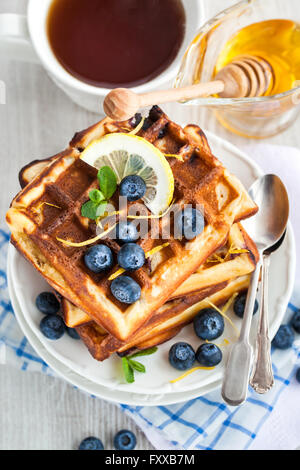 Lemon blueberry waffles with honey, zest, fresh berries and cup of tea - Stock Photo