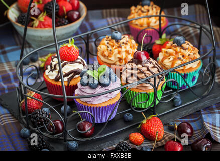 Set of different delicious cupcakes on dark - Stock Photo