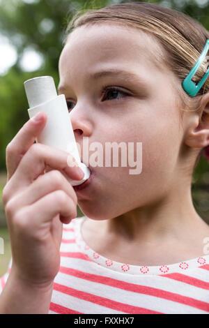 Girl using an asthma inhaler - Stock Photo