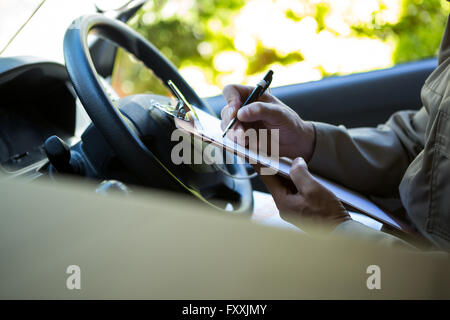 Delivery man sitting in his van - Stock Photo