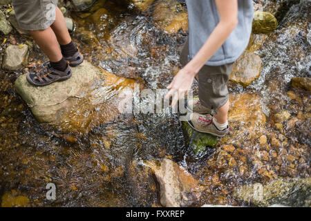Low section of hikers standing on rocks in stream - Stock Photo