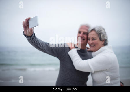 Senior couple taking a selfie on the beach - Stock Photo