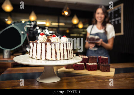 Smiling barista holding plate with cake - Stock Photo