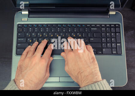 Man typing on a keyboard with letters in Hebrew and English - Laptop keyboard - Top View - Stock Photo