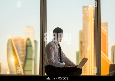Morning in business office. Back view of young man sitting on window with laptop, looking at beautiful dawn city - Stock Photo