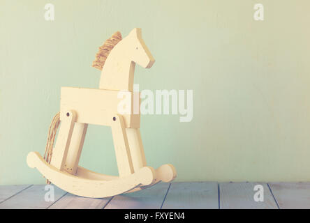 vintage rocking horse on wooden floor. retro filtered image - Stock Photo