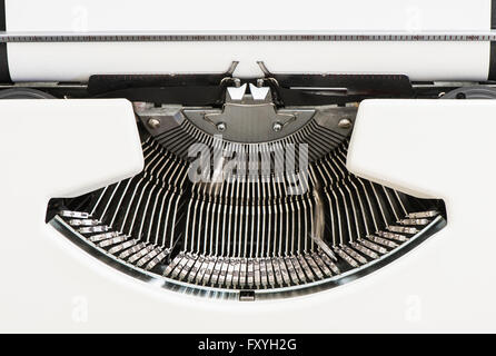 Detail view of an old fashioned typewriter from the 1970s with blank paper and moving hammer heads - Stock Photo