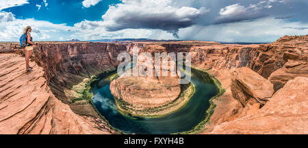 Tourist on a rock overlooking the Horseshoe Bend, bend of the Colorado River, King Bend, Glen Canyon National Recreation - Stock Photo