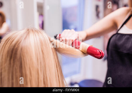 Unrecognizable hairdresser creating hairstyle for her beautiful - Stock Photo