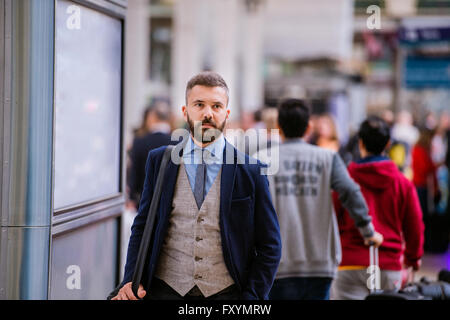 Hipster businessman in blue suit at the staition walking - Stock Photo