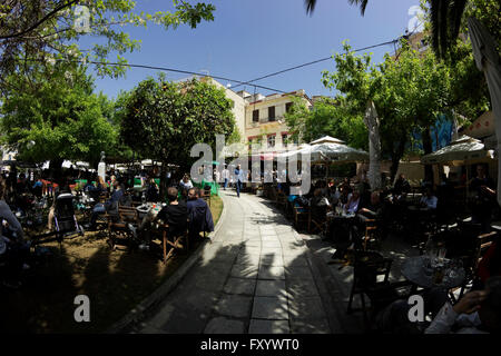 Greek cafe shops packed with people enjoying beverages under the shady trees of Karaoli square (plateia) walkway. - Stock Photo