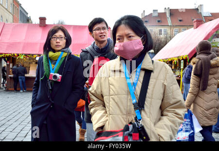 Prague, Czech Republic. Japanese tourists in Old Town Square, one wearing a surgical mask - Stock Photo