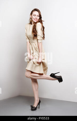 Attractive young woman in golden dress smiles and stands in fashion pose, she weares black high heels. She has long brown hair.