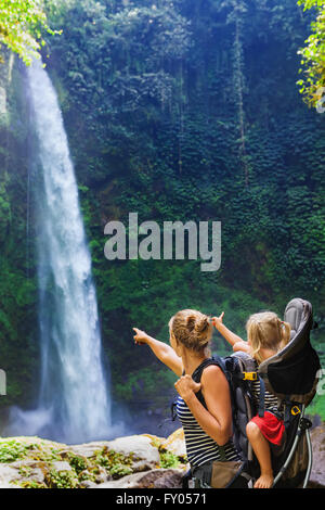 Young happy woman hold little traveller in back baby carrier, explore jungle waterfall in rainforest. - Stock Photo