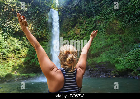 Beautiful young happy girl traveling in Bali wild forest spreading hands enjoying nature under tropical fresh waterfall. - Stock Photo