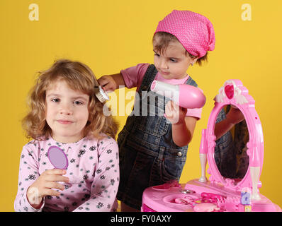 little girls play hairdressers - Stock Photo