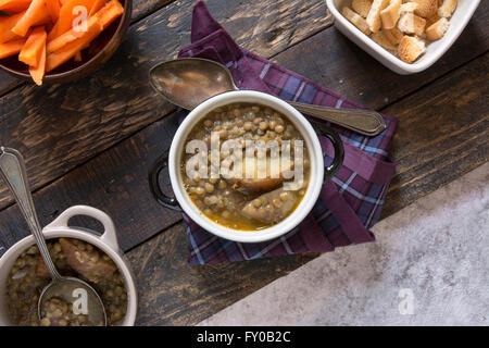 Homemade Brown Lentil Soup with Carrots Onions and Tomatos - Stock Photo
