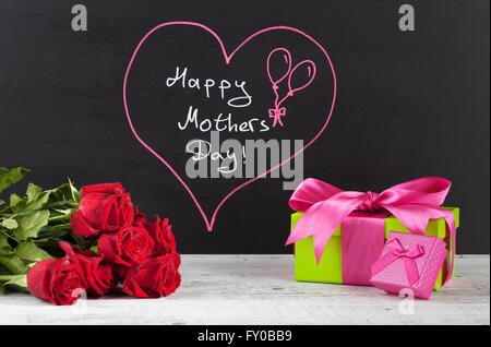 Happy Mother's day composition with red roses and pink gift boxes on white rustic wooden table. - Stock Photo