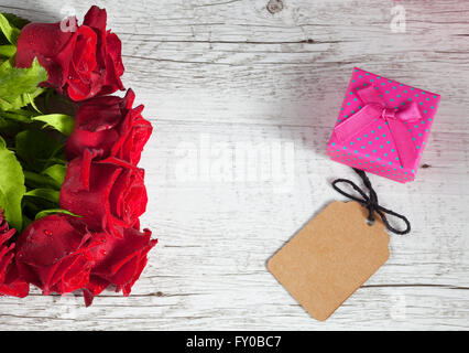 Red roses and small pink gift box with empty tag on white rustic wooden table. Top view with copy space. - Stock Photo