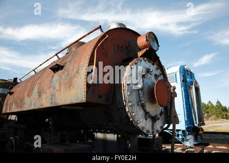 Photo of an old (circa 1890's) steam engine locomotive , with a modern rail car on the background. - Stock Photo