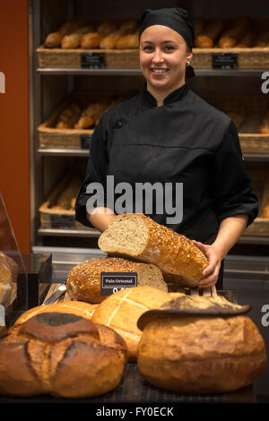 A smiling baker's wife presenting her loafs of bread. Bakery saleswoman in black uniform holding loaf of bread. - Stock Photo
