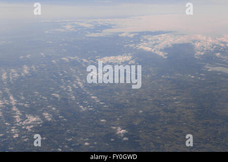 view from an aircraft window flying over the Alps towards Italy with another aeroplane way below. - Stock Photo