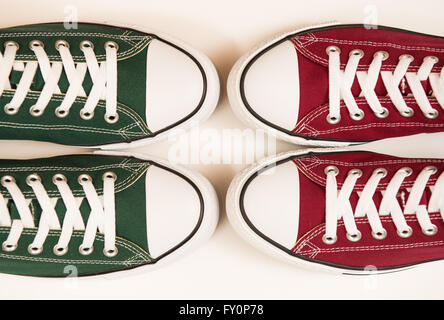 Green and maroon sneakers on a white background representing the colours of Hibernian and Heart of Midlothian football - Stock Photo