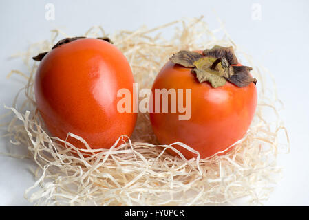 Two orange persimmons on a white table with straw - Stock Photo