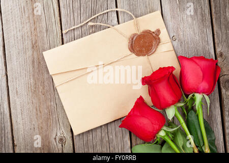 Love letter and red roses on wooden table. Valentines day concept - Stock Photo