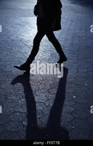 Silhouette of unrecognizable young woman walking in sunset shadows in the evening. Blue night shadows series. - Stock Photo