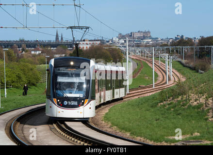 Edinburgh tram on route from the city centre to the airport with Edinburgh castle in the distance. - Stock Photo