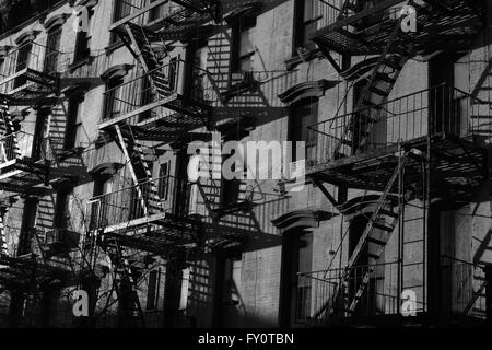 Fire escapes on old brick tenement building on Stanton Street, Lower East Side, New York City. Monochrome, black - Stock Photo