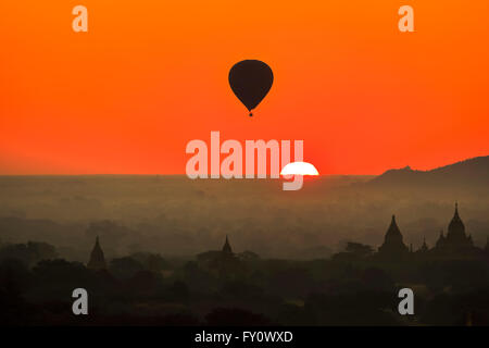 Sun rising over the horizon and hot air balloon flying at Old Bagan with orange sky and temple silhouettes, Myanmar - Stock Photo