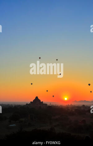 Sun rising over Dhammayangyi Temple and hot air balloons, Old Bagan with blue and orange sky and temple silhouettes, - Stock Photo