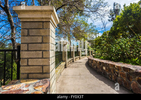 concrete walkway with stone walls, wrought iron railing - Stock Photo