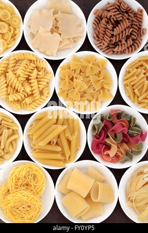 Italian pasta  shapes in white porcelain bowls. - Stock Photo